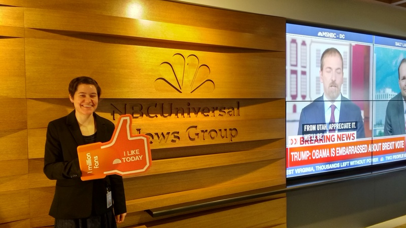 "A picture of me in front of a TV and a NBCUniversal News Group sign, smiling and holding a foam ""thumbs up"" on my hand."